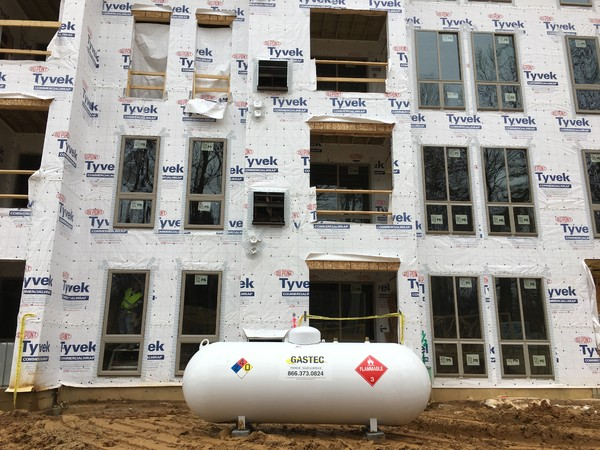This propane tank is being used at a construction site to provide temporary heating.  The building is near finished, and while there is no snow, the cold temperatures would have slowed down the building crew, if it were not for the propane service provided by GasTec